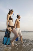 Man and woman carrying snorkeling gear