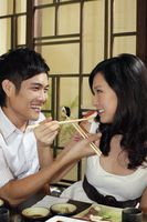 Man and woman feeding each other with japanese food
