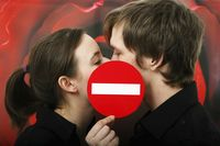 Man and woman kissing with no entry sign blocking