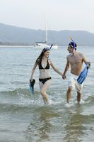 Man and woman running through water, holding flippers