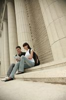 Man and woman sitting on stairs reading book