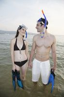 Man and woman walking on beach with snorkeling gear