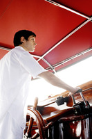 Man at helm of yacht