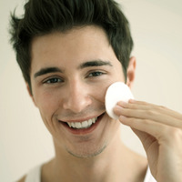 Man cleaning his face with cotton