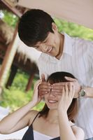 Man covering woman's eyes with hands