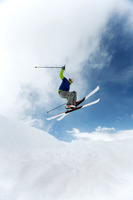 Man doing a mid air ski jump off a mountain