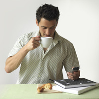 Man drinking coffee while text messaging on the mobile phone