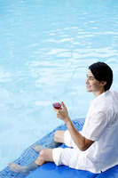Man enjoying a glass of red wine by the pool side