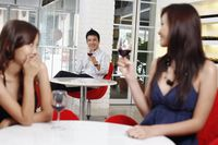 Man flirting with woman sitting at another table