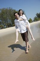 Man giving woman a piggy back ride on beach