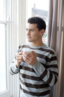 Man holding a cup of coffee while enjoying the view from the window