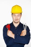 Man holding adjustable wrench and spanners