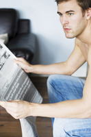 Man holding newspaper while thinking
