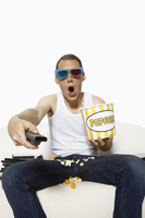 Man in 3d glasses watching television and eating popcorn