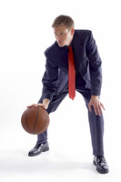 Man in business suit dribbling a basketball