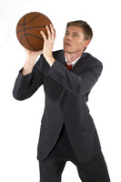Man in business suit trying to shoot a basketball