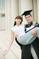 Man in graduation gown carrying woman in his arms