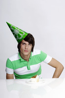 Man in party hat with a piece of cake in front of him