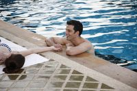 Man in swimming pool flirting with woman
