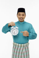 Man in traditional clothing holding up a clock