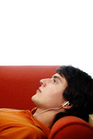 Man lying on the couch listening to music on the earphones