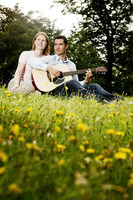 Man playing guitar for his girlfriend while sitting in the park