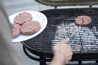Man putting beef patties on the barbeque grill