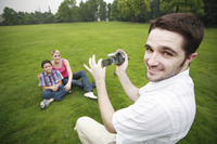 Man recording images of boy and girl