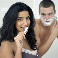 Man shaving his face while his girlfriend is brushing teeth
