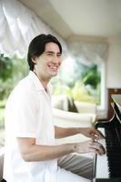 Man smiling while playing piano