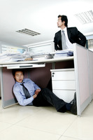 Man trying to find his worker who is sleeping under the desk