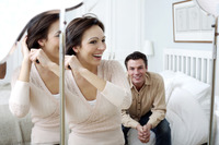 Man watching his wife brushing her hair