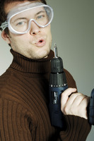 Man with goggles blowing a drill