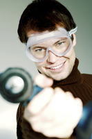 Man with goggles pointing a drill at the camera