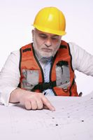 Man with hardhat pointing at blueprint