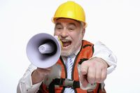 Man with hardhat pointing while shouting into megaphone