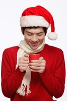 Man with santa hat holding a cup of hot coffee