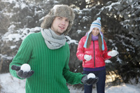 Man with snowballs in hands, woman standing in the background