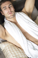 Man with towel lying on the bed daydreaming