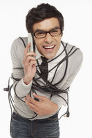 Man wrapped in a tangled cable talking on the phone