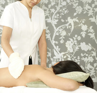 Massage therapist cleaning woman's back