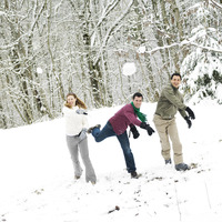 Men and woman throwing snowballs at the camera