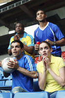 Men and woman watching soccer match in stadium