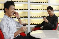 Men enjoying wine, another man is talking on the phone
