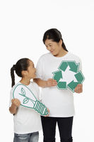 Mother and daughter holding up a recycle logo as well as a cut out light bulb
