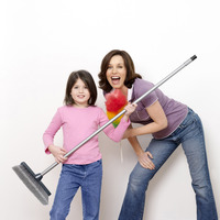 Mother and daughter with broom and feather duster