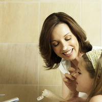 Mother applying a dab of facial scrub on daughter's nose