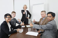 Multiethnic business people giving thumbs up in meeting