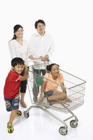Parents pushing a shopping cart with children in tow