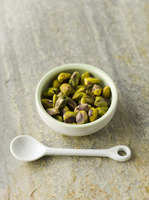 Pistachios in green bowl with white spoon